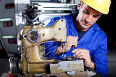 Mechanic repairing sewing machine Royalty Free Stock Images