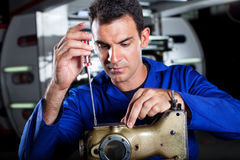 Mechanic repairing sewing machine Stock Photo