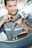 Mechanic repairing throttle twist grip. Mechanic repairing a throttle twist grip Royalty Free Stock Photo