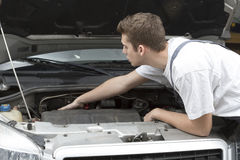 Mechanic repairing under car hood Stock Photography