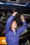 Mechanic Repairing Under Lifted Car Royalty Free Stock Images