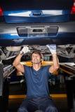 Mechanic Repairing Underneath Car. Male mechanic repairing underneath lifted car at garage stock images