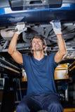 Mechanic Repairing Underneath Car. Male mechanic repairing underneath lifted car at garage royalty free stock image
