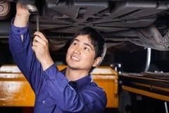 Mechanic Repairing Underneath Lifted Car. Happy male mechanic repairing underneath lifted car at auto repair shop stock image