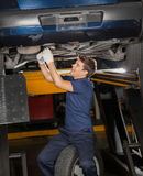 Mechanic Repairing Underneath Lifted Car. Young male mechanic repairing underneath lifted car at auto repair shop stock image
