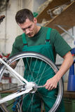 Mechanic repairing wheel on a bicycle in workshop Stock Photo