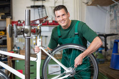 Mechanic repairing wheel on a bicycle in workshop Royalty Free Stock Photography