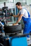 Mechanic repairman balancing  car wheel Royalty Free Stock Photo