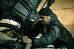 Mechanic repairs the car stock image