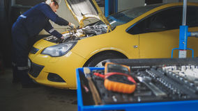 Mechanic repairs a car - unscrews detail of automobile - garage service Stock Image