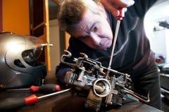 Mechanic repairs a carburetor. Mechanic repairs the carburetor of his motorcycle Royalty Free Stock Images