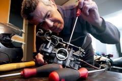 Mechanic repairs a carburetor. Mechanic repairs the carburetor of his motorcycle Royalty Free Stock Image