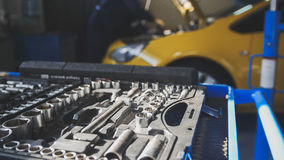 Mechanic repairs yellow car in professional auto service, de-focused Royalty Free Stock Image