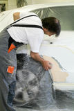 Mechanic reparing a car in auto repair shop Royalty Free Stock Photography