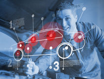 Mechanic reparing car while consulting futuristic interface. In blue royalty free stock image