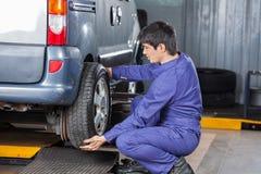 Mechanic Replacing Car Tire At Repair Shop Stock Photo