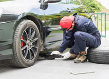 Mechanic replacing lug nuts changing tires on vehicle Royalty Free Stock Photo