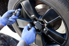 Mechanic replacing the plastic wheel. Cover after rotating the tires Stock Images