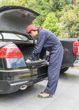 Mechanic replacing to the spare tire at the back of the car Royalty Free Stock Photos