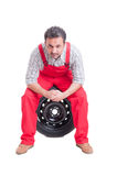 Mechanic resting and taking a break sitting on a tire Royalty Free Stock Photo