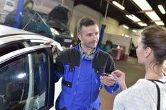 Mechanic returning key to car owner Stock Images
