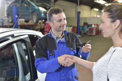 Mechanic returning key to satisfied client Stock Images