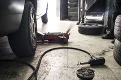 Mechanic rising a van. He is using a jack for tire change Royalty Free Stock Image