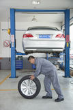 Mechanic Rolling Tire Stock Photography