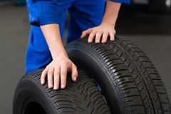 Mechanic rolling a tire wheel Royalty Free Stock Images