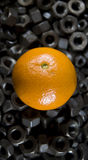 Mechanic's healthy lunch. A shot of an orange standing on a myriad of gritty nuts Stock Photo
