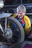 Mechanic sanding the motorcycle wheel spokes Royalty Free Stock Photo