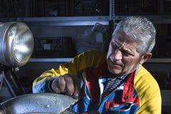 Mechanic sanding a mudguard Royalty Free Stock Photos