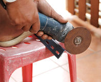 Mechanic sawing metal. Closeup image of mechanic sawing metal by electric saw on red chair Stock Photography