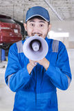 Mechanic is screaming with megaphone Stock Photo