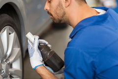 Mechanic with screwdriver changing car tire Stock Photography