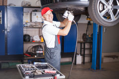 Mechanic screwing a tyre Stock Photography