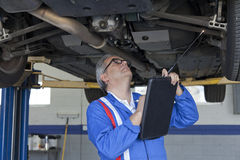Mechanic scrutinizing the car and writing down something on clipboard Stock Photo