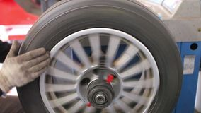 Mechanic in the service balances car wheel stock video