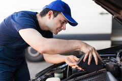 Mechanic servicing a car engine Stock Images