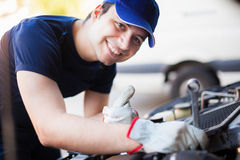 Mechanic servicing a car engine Royalty Free Stock Image
