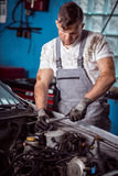 Mechanic servicing car Royalty Free Stock Images