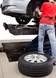Mechanic servicing a car with tyre on the ground Royalty Free Stock Image