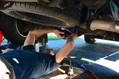 mechanic servicing under a truck royalty free stock images