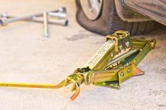 Mechanic sets a jack-screw. Stock Photo