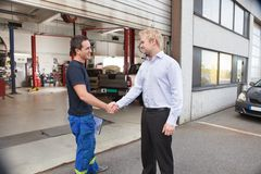 Mechanic shaking hands with client Royalty Free Stock Images