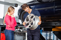 Mechanic Showing Alloy To Customer Royalty Free Stock Photos