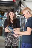 Mechanic showing bill to a woman Stock Photos