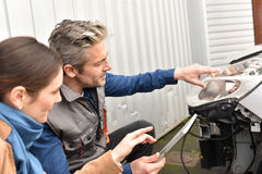 Mechanic showing client what needs to be repaired Stock Images