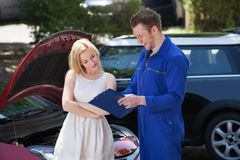 Mechanic showing clipboard to customer by breakdown car Royalty Free Stock Photos
