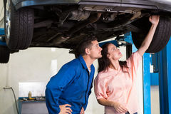 Mechanic showing customer the problem with car Royalty Free Stock Photos
